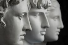 Gypsum Copy Of Ancient Statue Apollo, Antinous And Venus Head On Dark Textured Background. Plaster Sculpture Face.