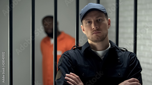 Canvas Print Prison warden looking to camera standing near cell with imprisoned afro-american