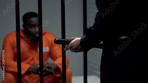 Valokuvatapetti Afro-american prisoner in cell looking at jail guard with baton, harassment