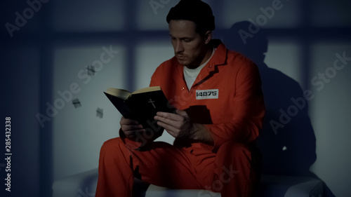 Imprisoned religious male reading bible, convicting in sins, feeling guilty Fototapet