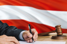 Judge Writing On Paper In Courtroom With Austria Flag Background. Wooden Gavel Of Equality Theme And Legal Concept.