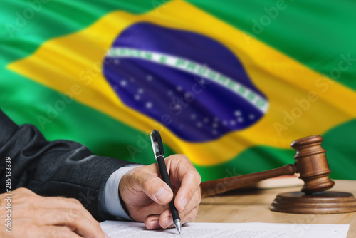 Photo Judge writing on paper in courtroom with Brazil flag background