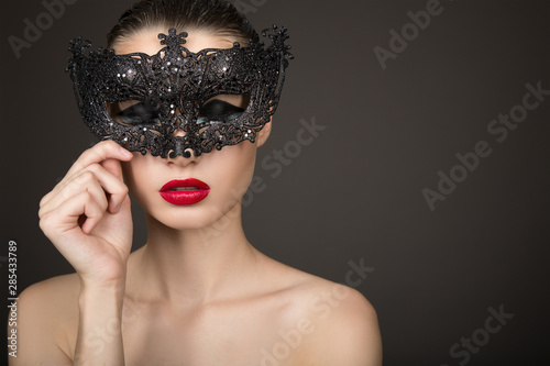 Fashion woman with long hair and red lipstick with a black mask. Dark background. Carnival, holiday - 285433789