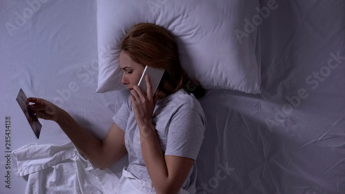 Crying woman lying in bed and looking at photo, calling her boyfriend, betrayal Canvas Print