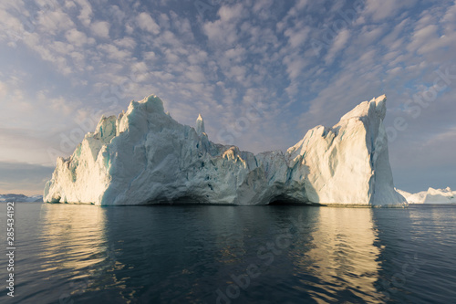 Foto op Aluminium Arctica Nature and landscapes of Greenland or Antarctica. Travel on the ship among ices. Studying of a phenomenon of global warming Ices and icebergs of unusual forms and colors Beautiful midnight sun on ship
