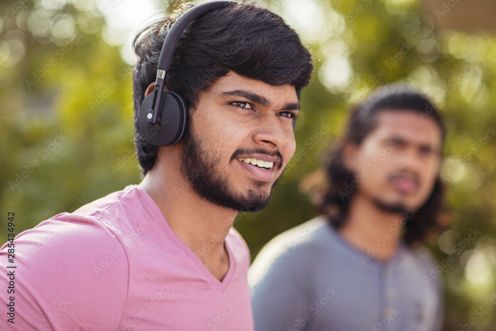 Fototapeta Young listening music in headphone with his friend