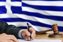 Judge Writing On Paper In Courtroom With Greece Flag Background. Wooden Gavel Of Equality Theme And Legal Concept.