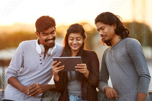 Cheerful young Indian friends playing in digital tablet Tapéta, Fotótapéta