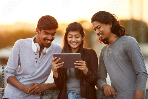 Photo  Cheerful young Indian friends playing in digital tablet