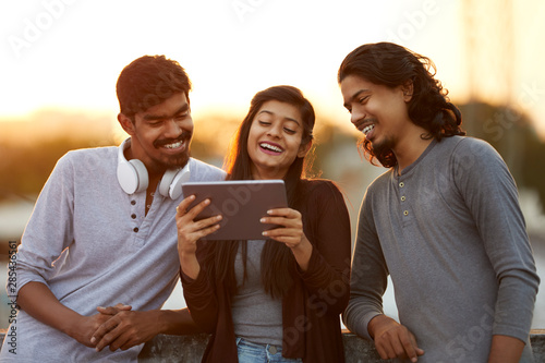 Fényképezés Cheerful young Indian friends playing in digital tablet