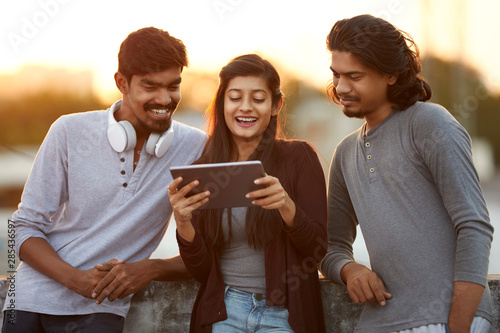Cheerful young Indian friends playing in digital tablet Canvas Print