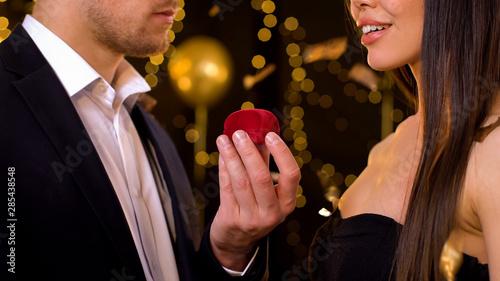 Fototapeta Male holding gift box with jewelry, presenting girlfriend for birthday at party obraz na płótnie