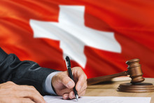 Judge Writing On Paper In Courtroom With Switzerland Flag Background. Wooden Gavel Of Equality Theme And Legal Concept.