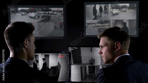 Fotografie, Obraz  Security guards watching crime scene on surveillance cameras, espionage concept