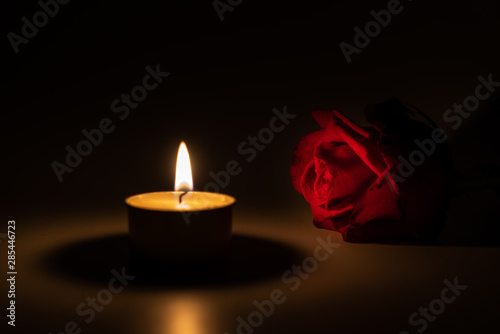 tealight candle and red rose at midnight Fototapeta
