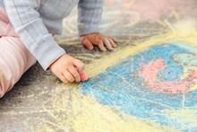 Child Draws Hand In Colored Ch...