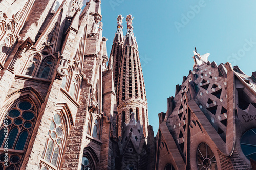Photo Sagrada Familia building exterior on hot summer day in Barcelona Spain with blue