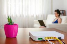 Modem Router On A Table In A Living Room. A Woman Using A Laptop While Sitting On The Sofa Is In Background.