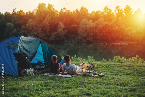 Spoed Foto op Canvas Kamperen young couple relaxing by the river. camping outdoor