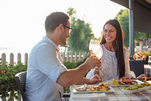 Beautiful Happy Young Couple Making A Toast, Celebrating Anniversary Or Birthday In A Restaurant. Husband And Wife Having Romantic Dinner In A Restaurant By The River
