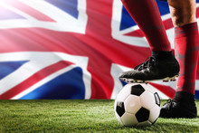 Close Up Legs Of United Kingdom Football Team Player In Red Socks, Shoes On Soccer Ball At The Free Kick Or Penalty Spot Playing On Grass.