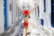 Weibliche Touristin mit Rucksack geht durch eine kleine, weiße Gasse mit blauen Fenstern auf den Kykladen in Griechenland