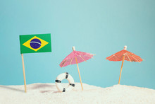 Miniature Flag Of Brazil On Beach With Colorful Umbrellas And Life Preserver. Travel Concept, Summer Theme.