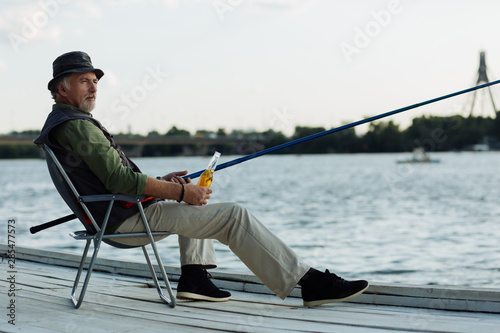 Fotobehang Vissen Pensioner chilling with bottle of beer while fishing