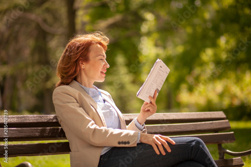 one mature woman, reading aloud while learning from book. Canvas Print