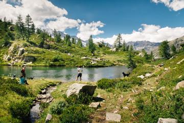 Mountain lake landscape with people near Bellagarda lake. Sense of freedom. Gran Paradiso National Park, Ceresole Reale, Piedmont, Italy