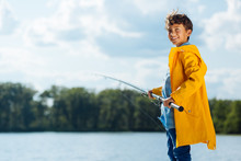 Boy Wearing Yellow Rain Coat Smiling While Fishing