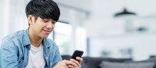 Panoramic Or Banner Of Happy Asian Teenager Using Smart Phone And Smiling On Sofa Living Room At Home. Asian Man Holding And Using Cellphone For Searching Data And Social Medie On Internet.
