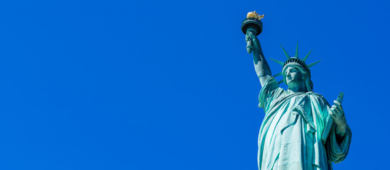 Panoramic of The Statue of Liberty in New York City. Statue of Liberty with blue sky over hudson river on island. Landmarks of lower manhattan New York city.