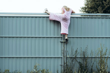 Girl Climbing Metal Fence Outd...