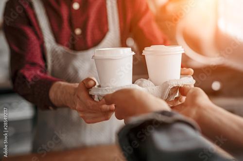 Fototapeta Barista serving coffee in takeaway cups in coffee shop obraz