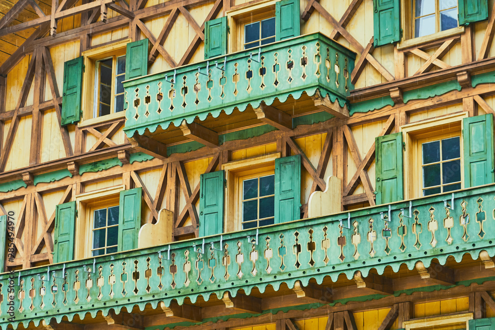Fototapeta Detailed view of a traditional Bavarian house with half-timbered house and green balconies made of wood