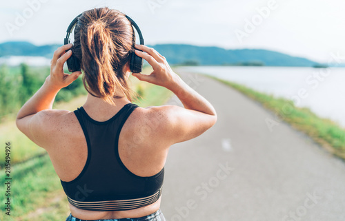 Fotografie, Obraz  Young teenager girl adjusting  wireless headphones before starting jogging and l