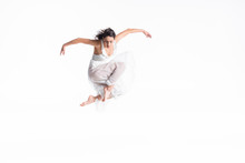 Beautiful, Graceful Ballerina In White Dress Jumping In Dance Isolated On White