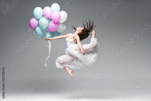 Tablou Canvas beautiful ballerina in white dress dancing with festive balloons on grey backgro