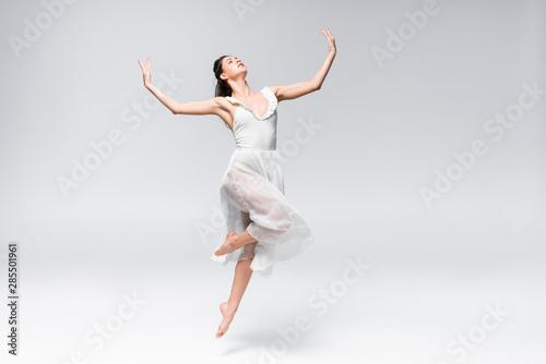 Fotografie, Obraz young elegant ballerina in white dress dancing on grey background
