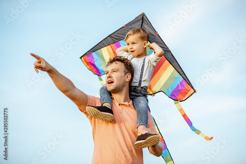 Portrait of a happy father and young son on the shoulders with colorful air kite on the blue sky background Wallpaper Mural