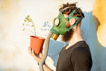 Portrait Of A Sad Man With Gas Mask Holding Dried Flowerpot On The Grey Rusty Background. Concept Of Poor Ecology, Air Pollution And Radiation Hazards