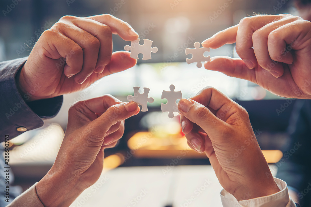Fototapeta Strategy and Solution Business Concept.Group of Business people holding piece of jigsaw puzzle to solution problem on wooden desk.Professional Businessman and Partnership meeting in office.