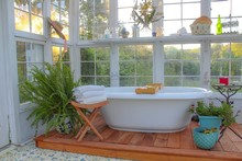 Interior Of A Beautiful Custom Built Greenhouse With A Large Soaking Tub Surrounded By Plants, With A Stenciled Mediterranean Style Floor And Beautiful Tole Chandelier, Selective Focus On Foreground