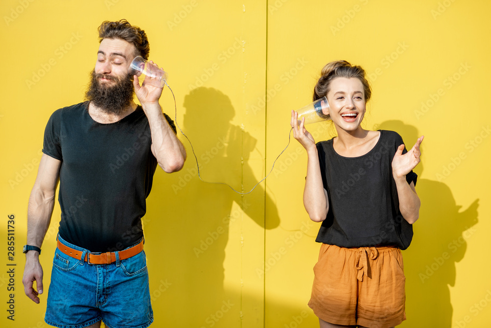 Fototapeta Man and woman talking with string phone made of cups on the yellow background. Concept of broken phone and bad communication