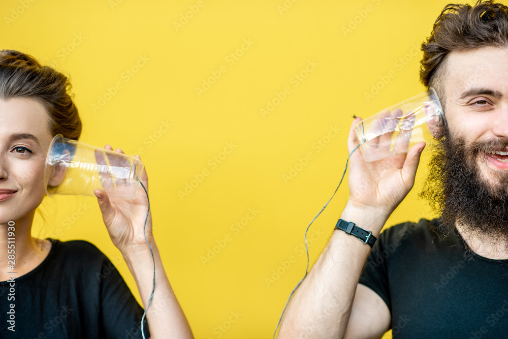 Fototapeta Man and woman talking with string phone made of cups on the yellow background. Concept of communication