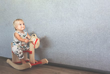 Cute Blond Baby Rides Wooden T...