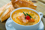 Cream salmon soup with carrots and potatoes served in bowl - 285515791
