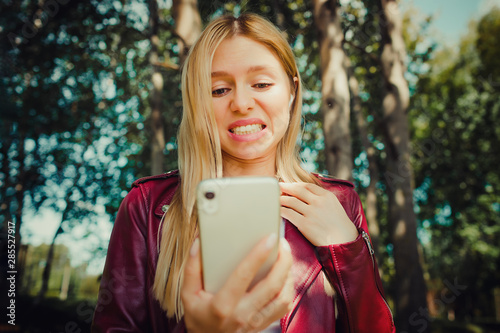 shock shout beautiful young pretty girl looking at the screen display of mobile Fototapet