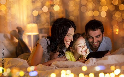 Obraz na plátně  people and family concept - happy mother, father and little daughter with tablet